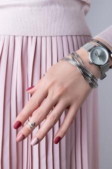 シルバージュエリーとアクセサリーで梨花の手。最小限のピンク春夏マニキュアデザインの女の子。