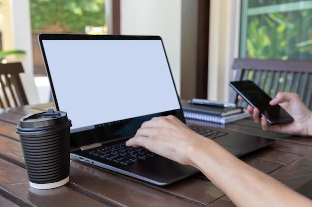 카페 나 집 테라스에서 스마트 폰, 커피 또는 차 종이 컵과 노트북 여자 손