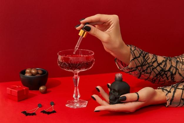 으스스한 네일 디자인을 가진 여자의 손은 빨간 테이블에 크랜베리 할로윈 칵테일을 요리합니다.