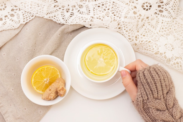 Womans hands with tea, lemon, ginger on white