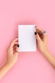 트렌디 한 핑크와 블랙 매니큐어 폴딩 종이로 여자의 손.