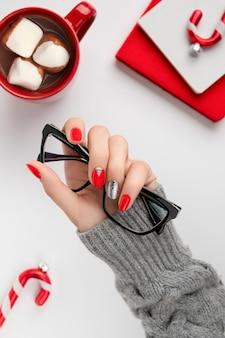 トレンディな赤いマニキュア保持メガネと女性の手