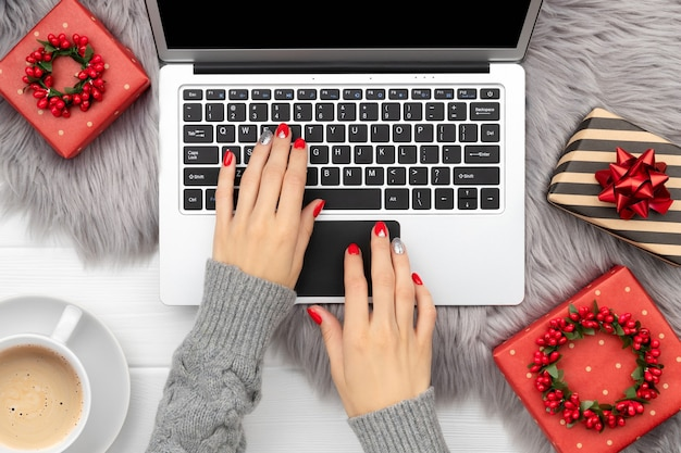 Womans hands with trendy red manicure typing on the keyboard