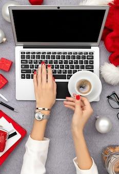 キーボードで入力するトレンディな赤いマニキュアと女性の手