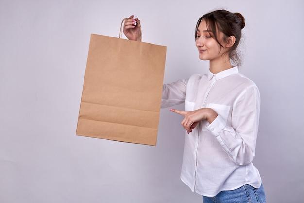종이 쇼핑백을 들고 가리키는 여자
