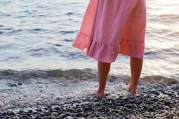 Женские ноги в розовом платье стоят босиком в воде на берегу морской гальки