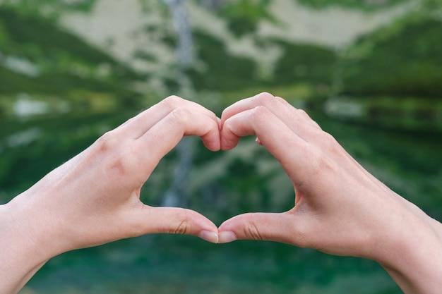 Женщины делают форму сердца руками на фоне гор недалеко от озера.