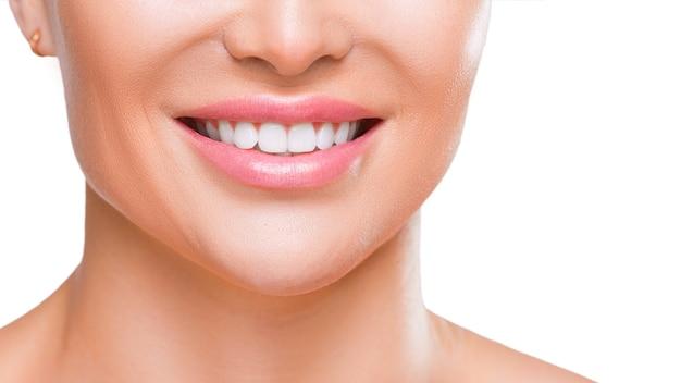 Улыбка женщины с белыми здоровыми зубами крупным планом на белом фоне