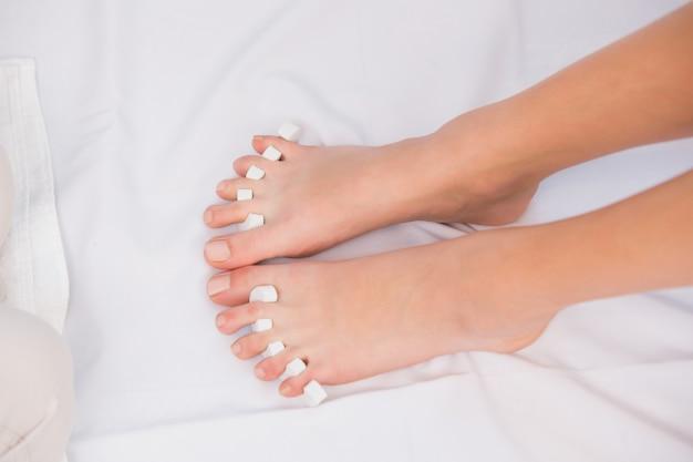 발가락 분리기로 분리 된 여자 발가락
