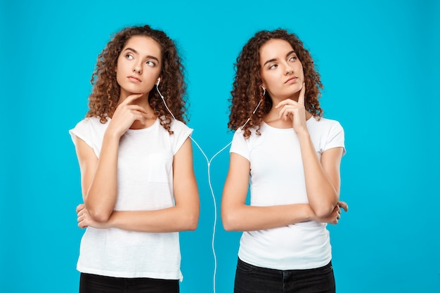 Womans twins listening music in headphones, thinking over blue.