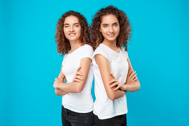 Womans twins posing with crossed arms, smiling over blue.
