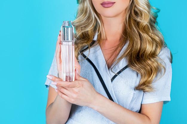 香水瓶を持つ女性。香水を使用している美しい少女。香水のボトルを持つ女性。女性は香水の香りを提示します。