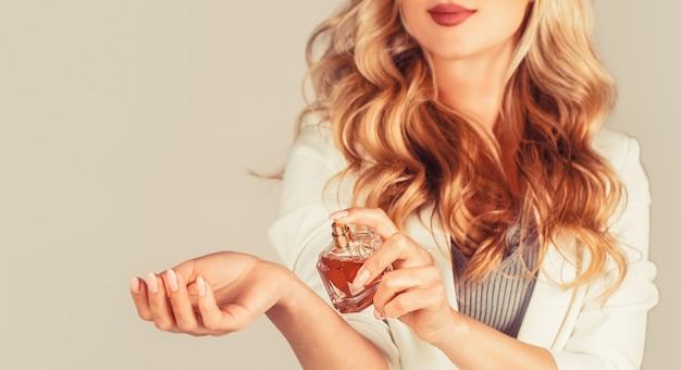 香水瓶を持つ女性。香水のボトルを持つ女性。