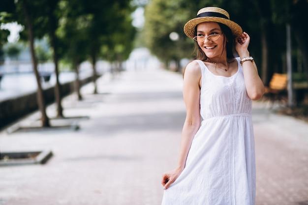 Womanwearingドレス、帽子、公園の外で