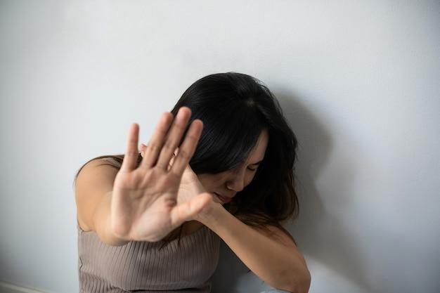 여성들은 집에서 두려움에 떨며 손을 들고 얼굴을 가린 채 학대했습니다. 여성에 대한 성희롱을 중지하십시오. 가족 개념의 폭력.
