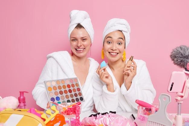 여성들은 화장품 광고에 화려한 아이섀도우 팔레트를 사용하여 블로그용 파운데이션 촬영 비디오를 보여주며 분홍색 스튜디오 벽에 격리된 목욕 가운을 입은 온라인 튜토리얼을 제공합니다.