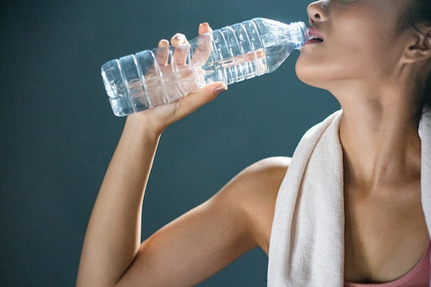Women after exercise drink water from bottles and handkerchiefs in the gym.