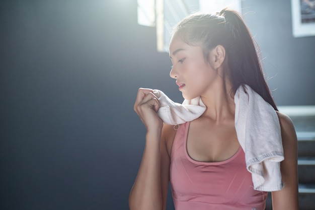 Women after exercising, wipe the face with a white cloth in the gym.
