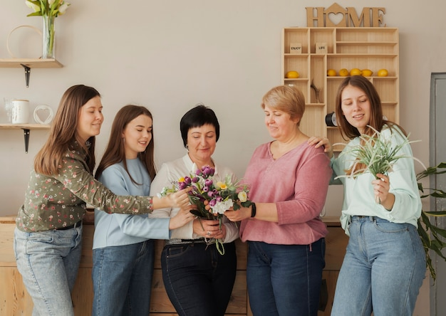 Women of all ages holding blooming flowers