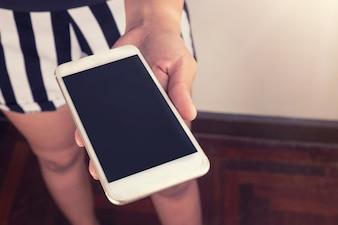 女性とスマートフォン、部屋の中の彼女の手に