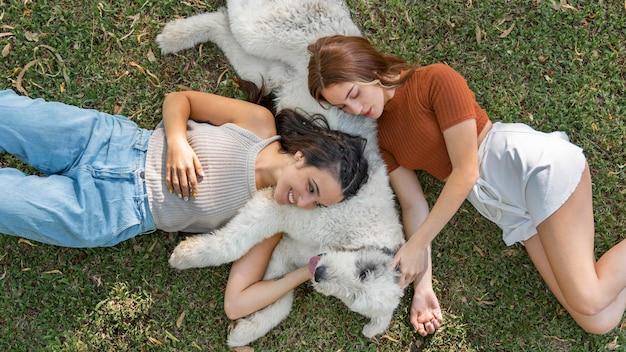 草の上に座っている女性と犬