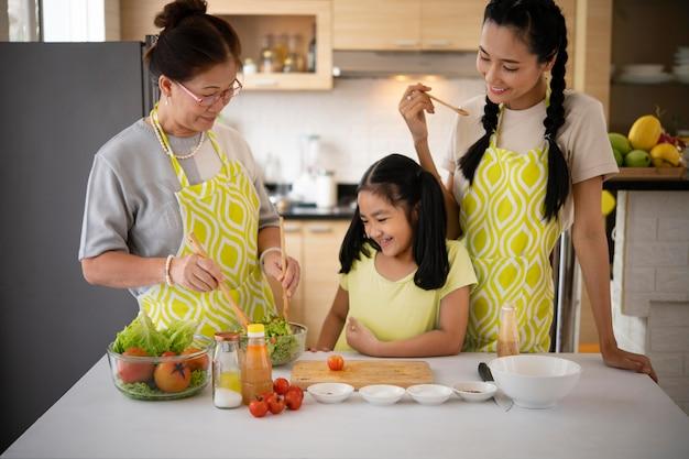 Женщины и девушка готовят еду