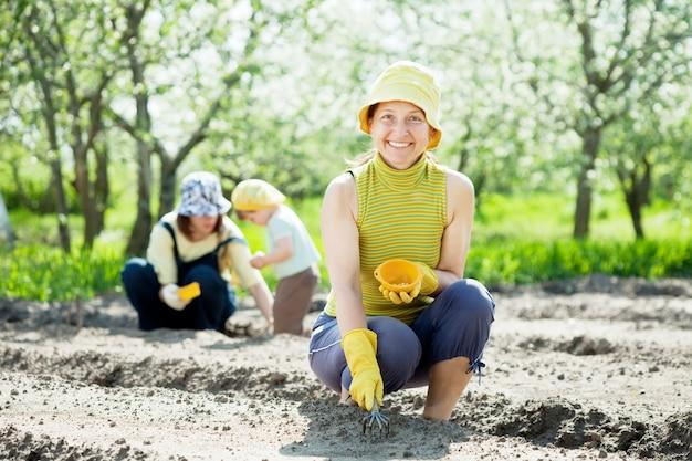 여자와 아이가 씨앗을 뿌리다