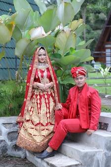 女性と男性は現代のイスラム教徒のインドのウェディングドレスを着ていますプレミアム写真