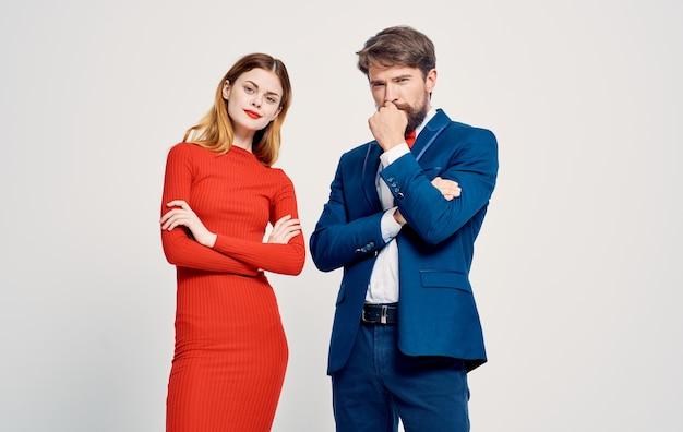 スーツを宣伝する手で身振りで示す明るい背景の上の女性と男性