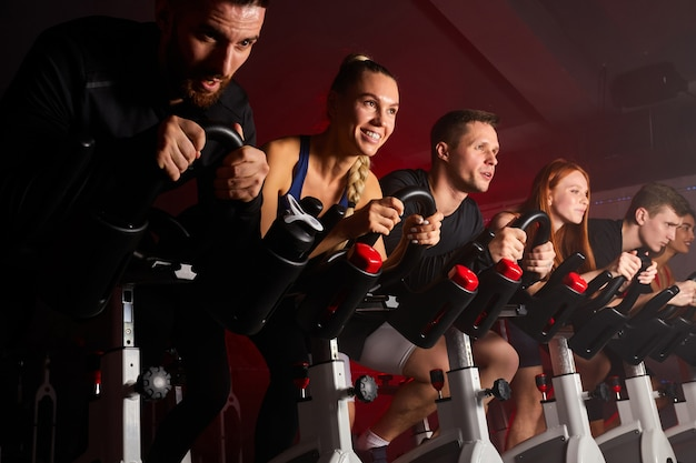 Женщины и мужчины на велотренажере тренируются в современном тренажерном зале, глядя вперед, вид сбоку на людей во время тренировки