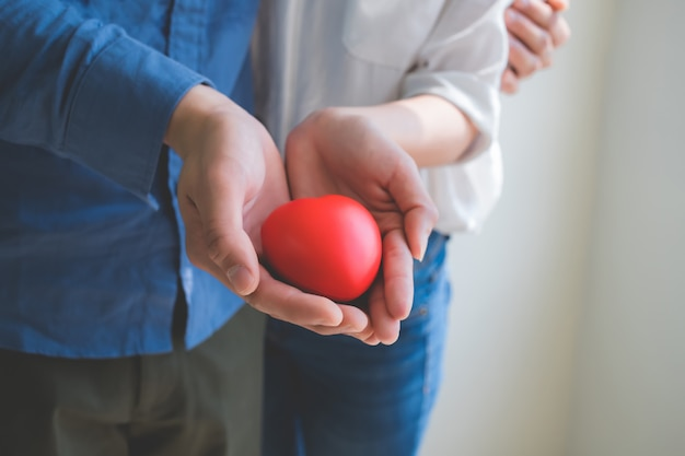 女性と男性は、お互いを愛し、お互いへの愛を維持するというコンセプトの中で、赤いハートで立っています。