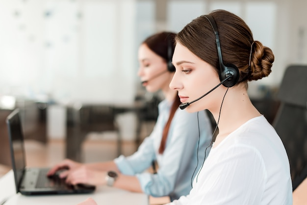 Women answering phone calls in the office with a head set