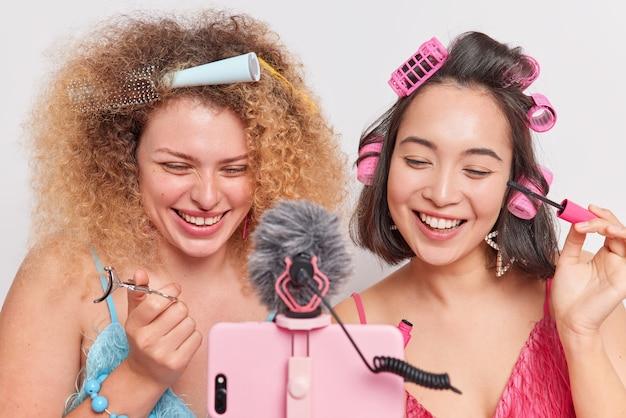 女性はマスカラを適用し、メイクアップレビュー美容製品フィルムプロセスを行う方法を示し、オンライン翻訳で三脚に携帯電話を使用します。
