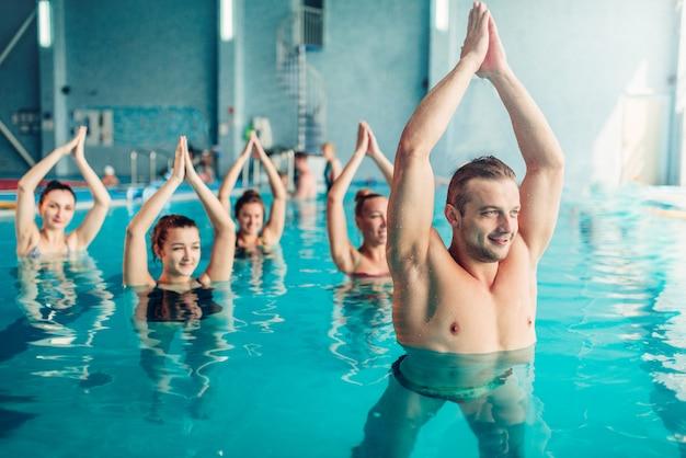 Занятия по аквааэробике у женщин на тренировках в центре водных видов спорта, крытом бассейне, рекреационном досуге
