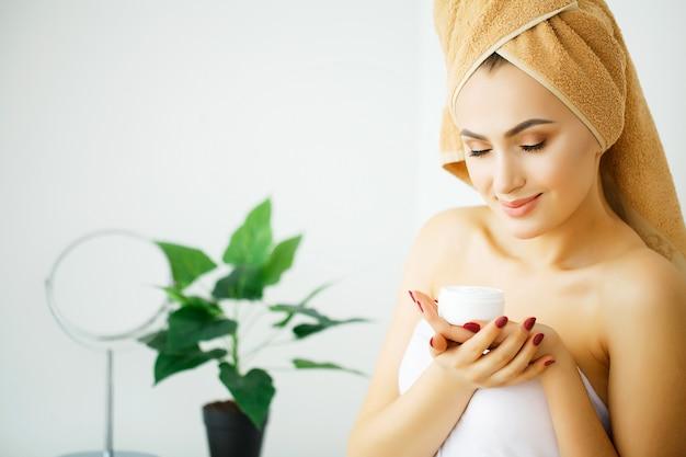 女性はバスルームで入浴後、クリームとローションを顔に塗ります。