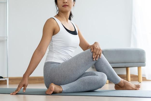 女性は健康と体を引き締めるために着席ツイスト運動を行っています。ヨガのコンセプト