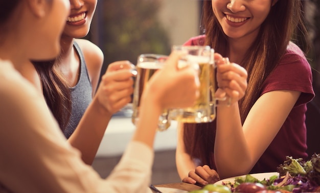 Women are drinking beer and the clink glasses in a restaurant