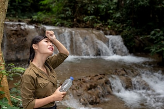 Women are hiking drinking fresh water in the forest
