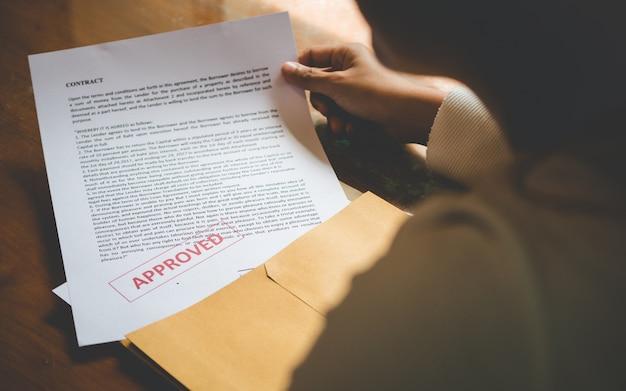 女性はビジネスで契約書に署名することについての封筒文書を開いている