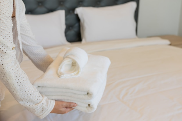 Women are placing small towels and white towels. on the hotel bed.
