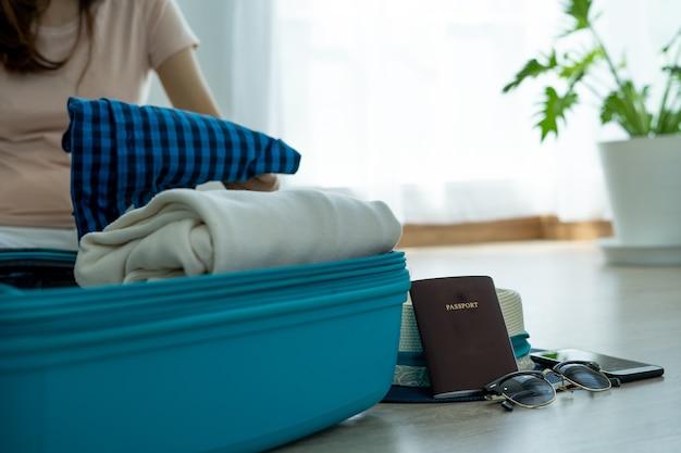 女性は、寝室で服やパスポート、さまざまな持ち物、旅行の入り口を準備しています。