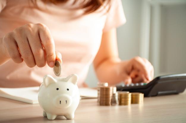 女性は利益のために成長し、将来のためにお金を節約するビジネスのために貯金箱にコインを入れています。退職コンセプトの計画