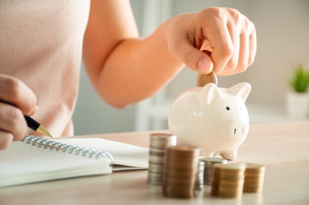 여성들은 이익을 위해 성장하고 미래를 위해 돈을 저축하는 사업을 위해 돼지 저금통에 동전을 넣고 있습니다. 은퇴 개념 계획