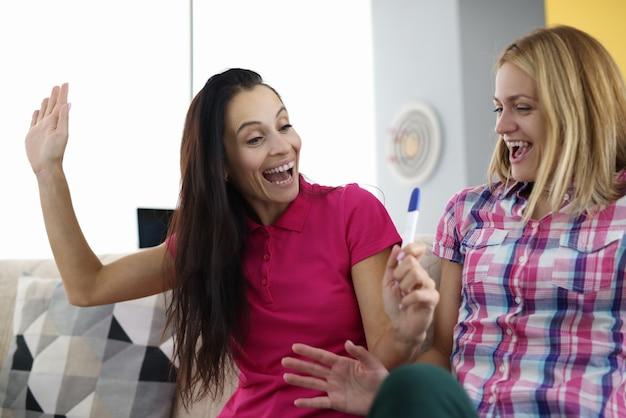 女性はソファに座って妊娠検査を見ています