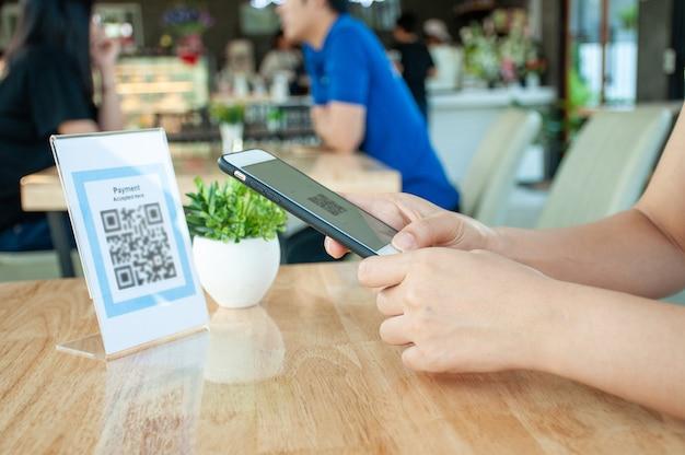 女性は携帯電話を使用してqrコードをスキャンし、食品の割引を受けたり、店舗で食品を購入したりしています。