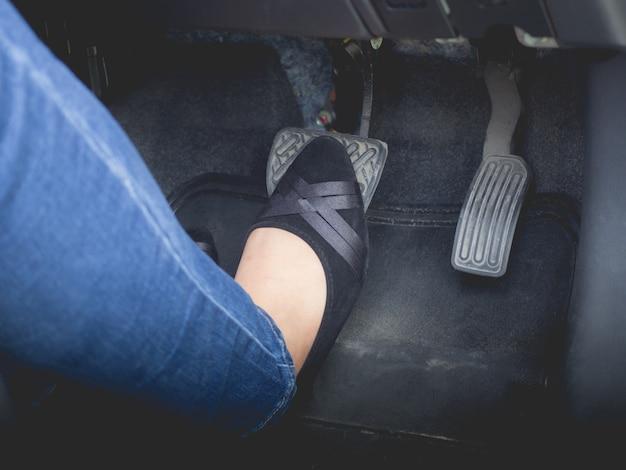 여자는 차를 제동하기 위해 발 페달을 사용하고 있습니다