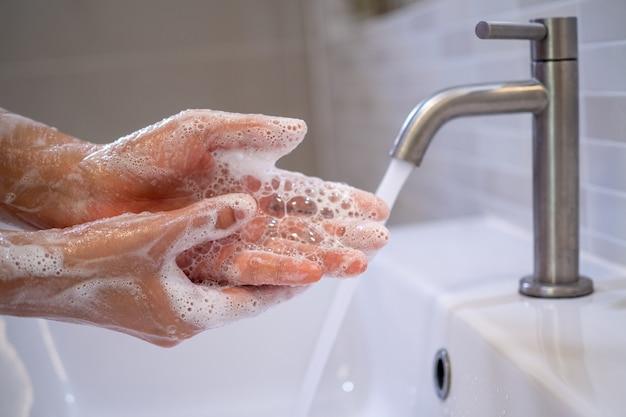 女性は泡石鹸ときれいな水で手を洗っています。手を洗って清潔に保ち、バイラルの拡散を防ぎます