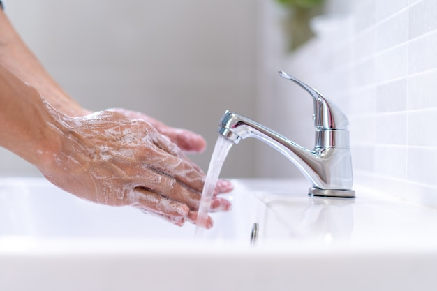 Women are washing their hands with foam soap and clean water. wash your hands to keep them clean and prevent the spread of viral