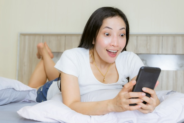 Women asian wow face smartphone on the bed