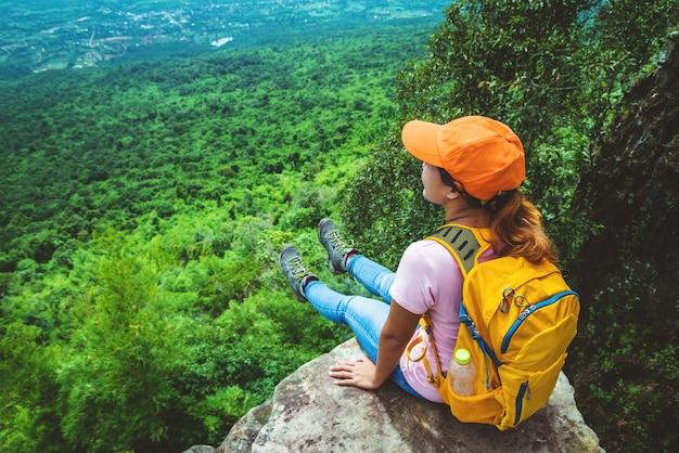 Женщины-азиаты путешествуют отдыхать в отпуске. сядьте на скалу. на moutain.